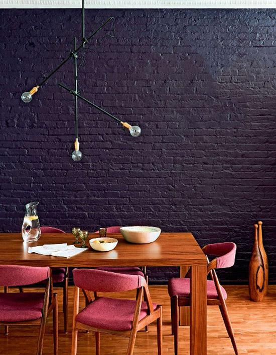 Black painted brick wall pink vintage chairs