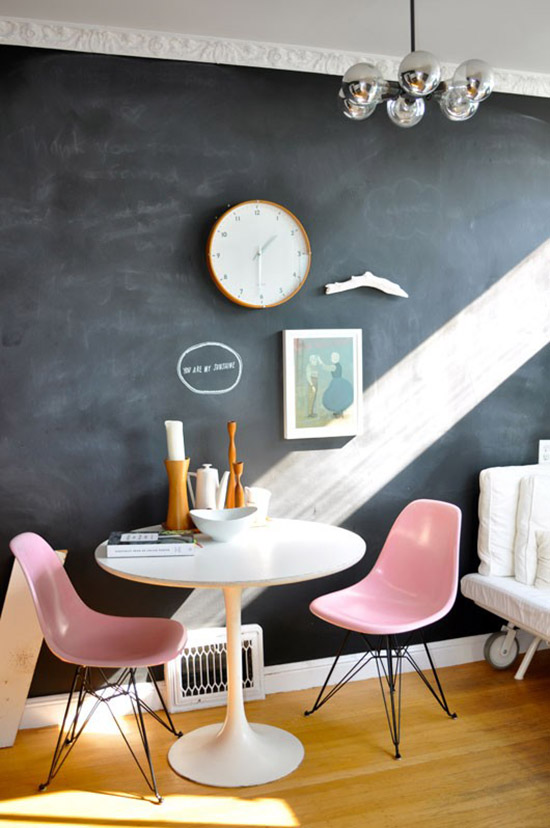 Pink Eames chairs and a chalkboard wall