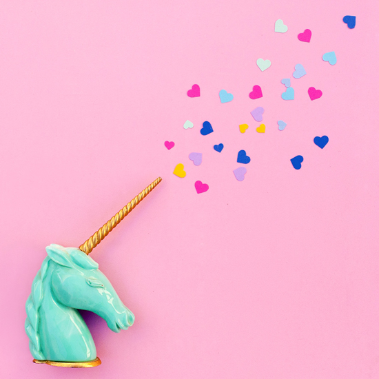 Teal unicorn with horn shooting heart confetti
